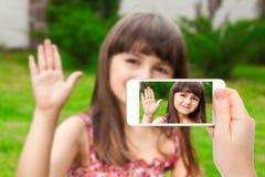 Vrouwelijke hand die een telefoon met videovraag van meisje op Th houden stock fotografie