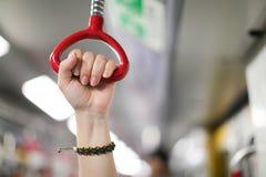 Vrouwelijke hand die een van een lus voorzien handvat in stedelijke openbaar vervoer lokale metro houden, ondergronds met vage ac royalty-vrije stock afbeeldingen
