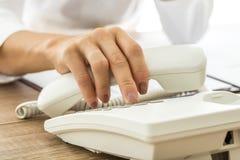 Vrouwelijke hand die een witte landline telefoonzaktelefoon en een diali houden stock fotografie