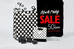 Vrouwelijke hand die een zwarte die giftdoos houden met zwart lint met witte stippen op het wordt verfraaid Stock Foto's