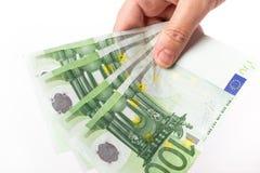 Vrouwelijke hand die 100 euro bankbiljetten houden Stock Foto