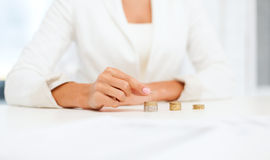 Vrouwelijke hand die euro muntstukken zetten in kolommen Stock Afbeeldingen