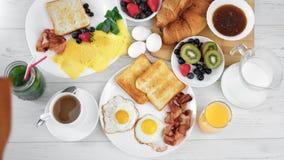 Vrouwelijke hand die gebraden ei op plaat met bacon en toost zetten die traditioneel ontbijtpov schot koken stock footage