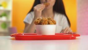 Vrouwelijke hand die gebraden kippenvleugels in tomatensaus, smakelijke ongezonde maaltijd onderdompelen stock footage