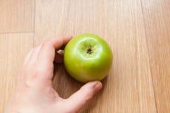Vrouwelijke hand die groene appel houdt Stock Afbeeldingen