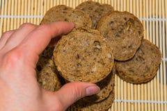 Vrouwelijke hand die het stuk van het volkorenmeel van het roggebrood houden stock foto's