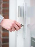Vrouwelijke hand die het zeer belangrijke opnemen in deurslot houden Stock Afbeeldingen