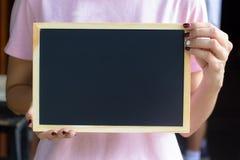 Vrouwelijke hand die klein bord, bord met leeg of c houden royalty-vrije stock foto