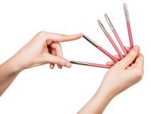 Vrouwelijke hand die kleurrijke die potloden voor lippen houden op wit worden geïsoleerd Royalty-vrije Stock Afbeeldingen