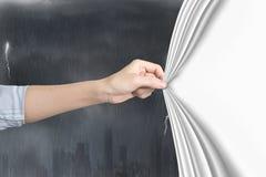 Vrouwelijke hand die leeg wit gordijn trekken die stormachtige stad bedekken royalty-vrije stock foto's