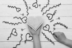 Vrouwelijke hand die met de hand gemaakt houten hart, hoogste mening houden Stock Afbeeldingen