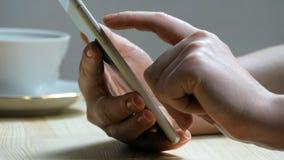 Vrouwelijke hand die mobiele telefoon thuis met behulp van - Smartphone Royalty-vrije Stock Foto's