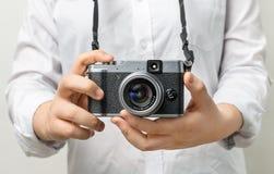 Vrouwelijke hand die moderne camera mirrorless camera houden Stock Afbeelding