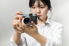 Vrouwelijke hand die moderne camera mirrorless camera houden Camera ter beschikking Nadrukcamera Stock Afbeeldingen