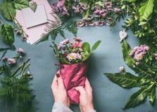 Vrouwelijke hand die mooi boeket van roze bloemen op bloemistwerkruimte maken, hoogste mening Het boeket van de vrouwenomslag in  royalty-vrije stock fotografie