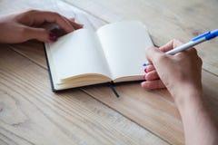 Vrouwelijke hand die nota's in een notitieboekje maken stock afbeelding