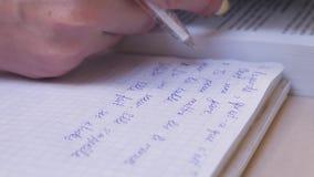 Vrouwelijke Hand die Nota's in Notitieboekje maken terwijl het Bestuderen van het Frans stock footage