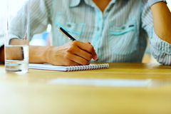 Vrouwelijke hand die op een document schrijven stock foto's