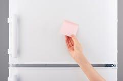 Vrouwelijke hand die roze document nota over witte ijskast houden Royalty-vrije Stock Afbeelding