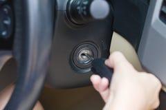 Vrouwelijke hand die sleutel in auto zetten Stock Foto's