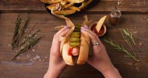 Vrouwelijke hand die traditionele Amerikaanse hotdog op de houten raad houden Hoogste mening Stock Afbeelding