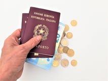 Vrouwelijke hand die twee Italiaanse paspoorten houden stock afbeeldingen