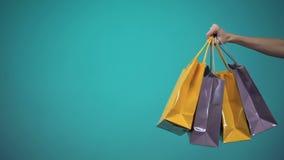 Vrouwelijke hand die vele kleurrijke het winkelen zakken op blauwe achtergrond, malplaatje houden stock footage