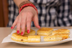Vrouwelijke hand die voor een cake bereikt Stock Foto's