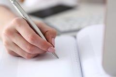 Vrouwelijke hand die zilveren pen klaar houden om nota te maken Stock Foto's
