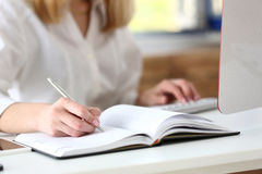 Vrouwelijke hand die zilveren pen klaar houden om nota te maken Stock Afbeelding