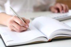 Vrouwelijke hand die zilveren pen klaar houden om nota te maken Royalty-vrije Stock Foto