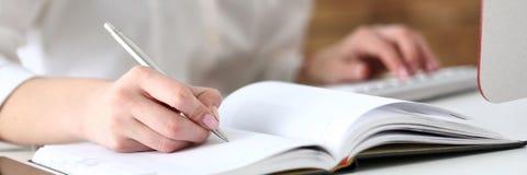 Vrouwelijke hand die zilveren pen klaar houden om nota te maken Royalty-vrije Stock Afbeelding