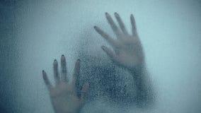 Vrouwelijke hand en hoofd, griezelige schaduwen op de glasmuur, in volledige HD, de scène van de Verschrikkingsfilm stock videobeelden