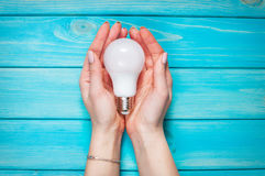 Vrouwelijke hand geselecteerde geleide lamp op blauwe houten achtergrond Stock Afbeelding