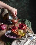 Vrouwelijke hand gietende olie over gebakken zalmlapje vlees met citroen en ui Royalty-vrije Stock Foto