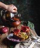 Vrouwelijke hand gietende olie over gebakken zalmlapje vlees met citroen en ui Royalty-vrije Stock Foto's