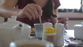 Vrouwelijke Hand het Bewegen Suiker of Melk in een kop van Hete Koffie of Thee Sluit omhoog stock footage