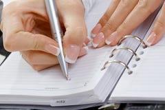 Vrouwelijke hand het schrijven nota's Stock Fotografie