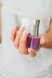 Vrouwelijke hand met de flessen van de spijkervernis Stock Foto