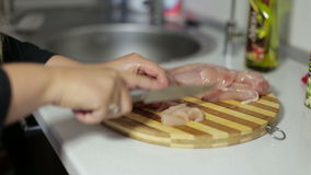 Vrouwelijke hand met een de kippenborst van de messenbesnoeiing op een scherpe raad stock videobeelden