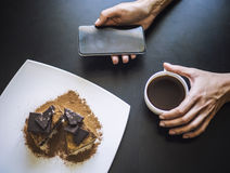 Vrouwelijke hand met een Kop van koffie, een telefoon en een mooie CH stock afbeeldingen