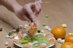 Vrouwelijke hand met een plak van mandarijnen stock foto's