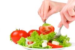 Vrouwelijke hand met een vork in de salade Stock Fotografie