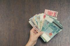 Vrouwelijke hand met geld van Zuidoost-Azië Munt van Hong Kong, Indonesië, Maleisië, Thai, de dollar van Singapore reis concept Stock Fotografie
