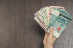 Vrouwelijke hand met geld van Zuidoost-Azië Munt van Hong Kong, Indonesië, Maleisië, Thai, de dollar van Singapore reis concept Stock Foto
