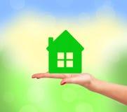 Vrouwelijke hand met klein model van huis over heldere aard Royalty-vrije Stock Foto's