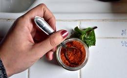 Vrouwelijke hand met lepel in een kruik Stock Foto