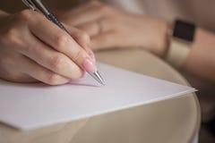 Vrouwelijke hand met pen het schrijven stock foto's