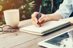 Vrouwelijke hand met potlood die op notitieboekje schrijven Vrouwenhand met pen stock afbeelding