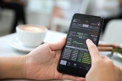 Vrouwelijke hand met smartphone handelvoorraad online in koffiewinkel, Bedrijfsconcept royalty-vrije stock fotografie